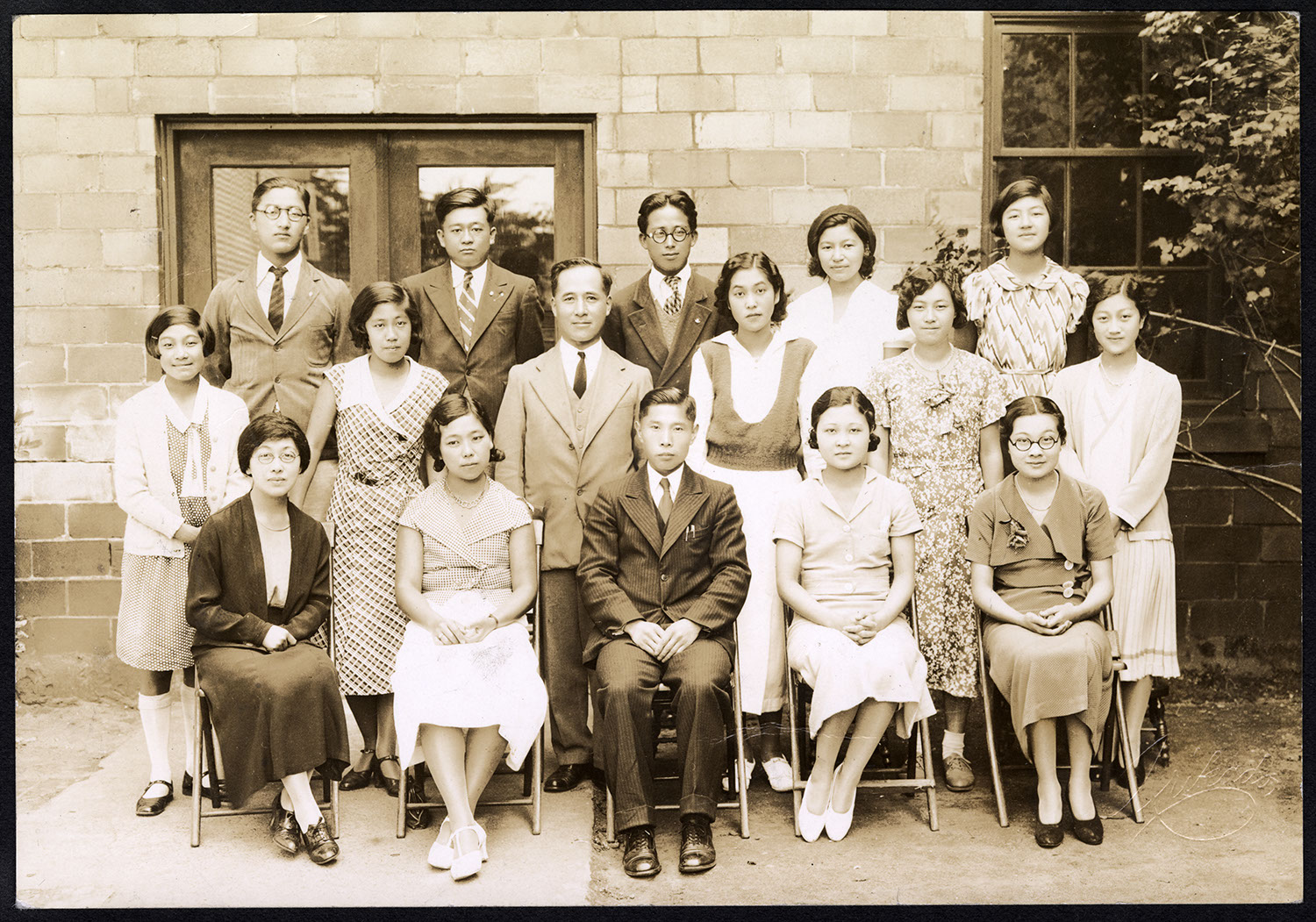 Rev. K. Shimizu with young people in front of Powell Street gymnasium
