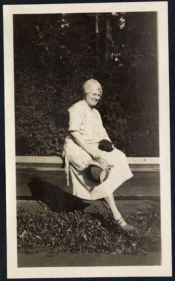 [Etta DeWolfe?] sitting on a fence