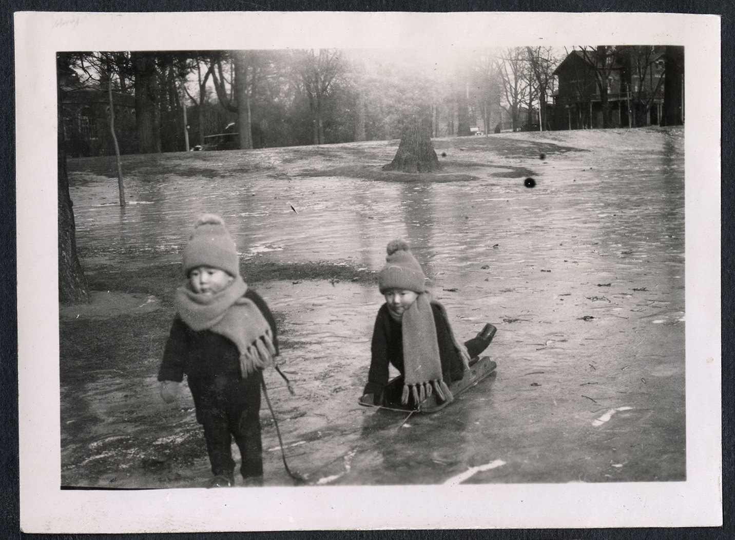 Two little children playing with a sled