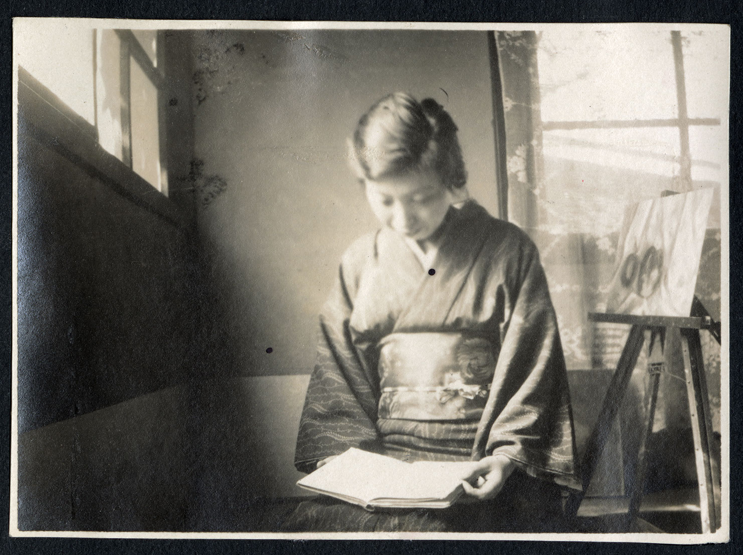 A woman in kimono reading a book