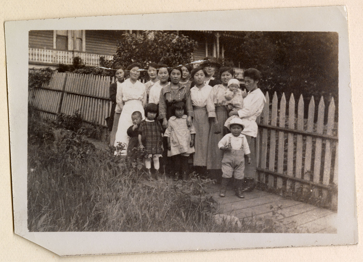 Women and children by a fence