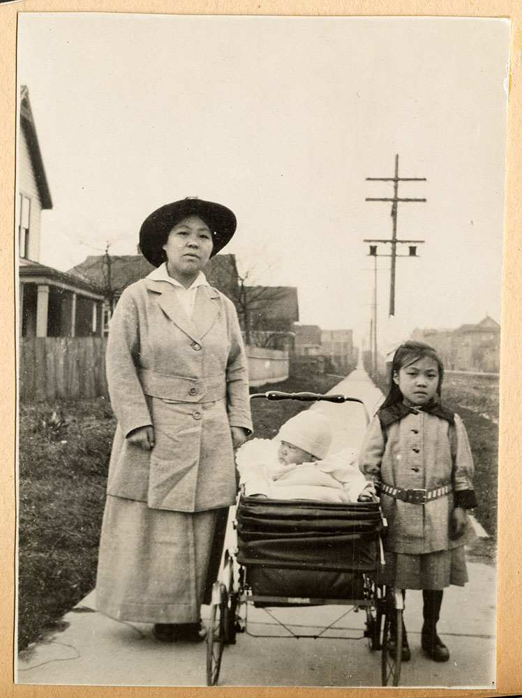 Unidentified woman with two children on the sidewalk