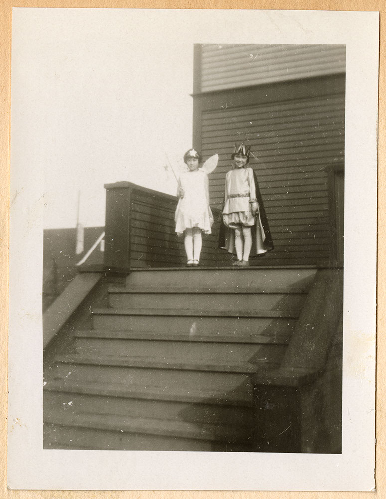 Two little girls in costumes on church steps
