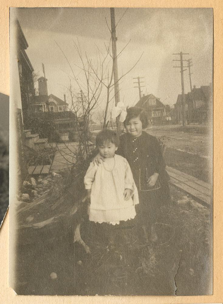 Two little girls by a sidewalk