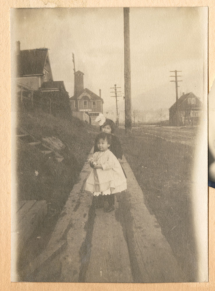 Two little girls on a sidewalk