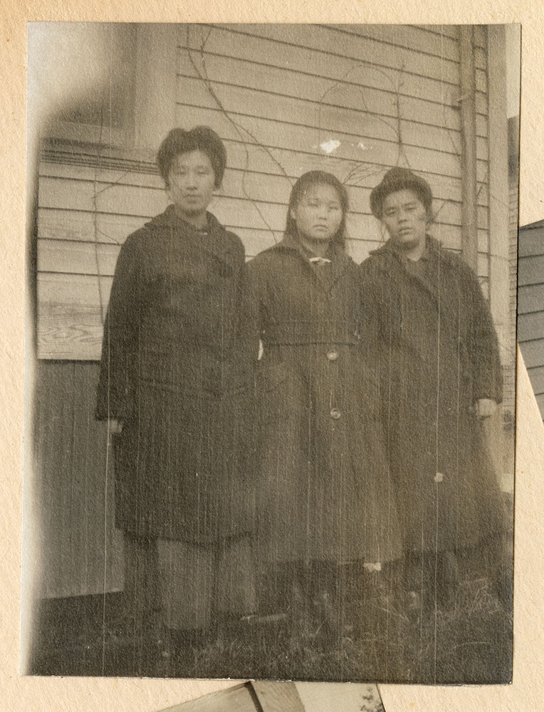 Three young women by a house
