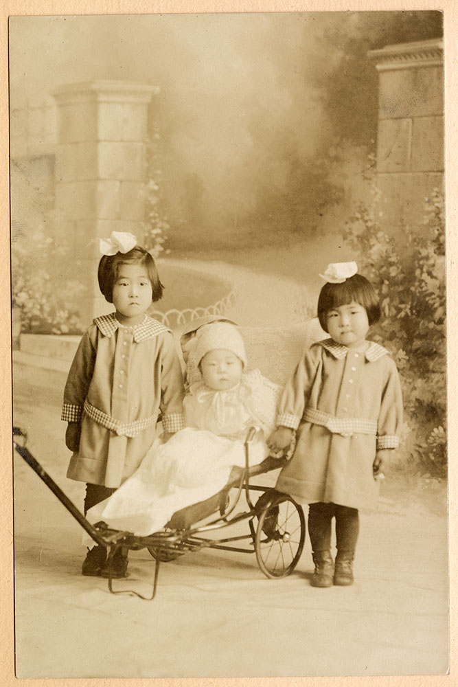Formal portrait of two little girls and a baby in a stroller